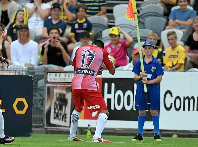 Tim Cahill of Melbourne City celebrates while the ball boy holds the corner flag out of his way.