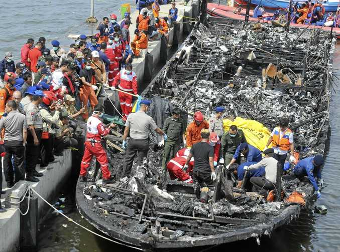 Rescuers search for victims in the wreckage of a ferry that caught fire off the coast of Jakarta.