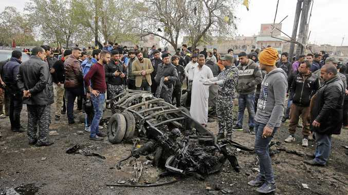 Security forces and citizens inspect the scene after a car bomb explosion at a crowded outdoor market in the Iraqi capital's eastern district of Sadr City.