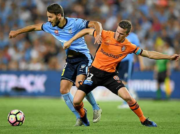 Milos Ninkovic of Sydney is tackled by Matt McKay of the Roar.