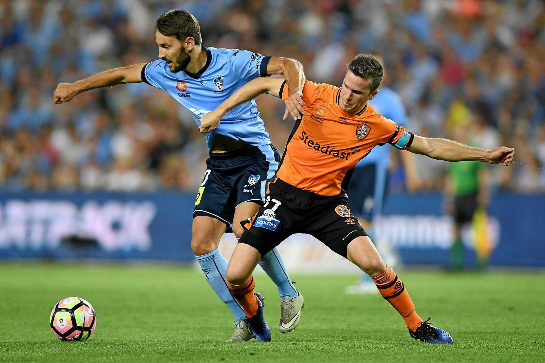 Milos Ninkovic of Sydney is tackled by Matt McKay of the Roar.