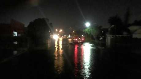 Cars attempts to cross flood water on Juliet St in Mackay's CBD