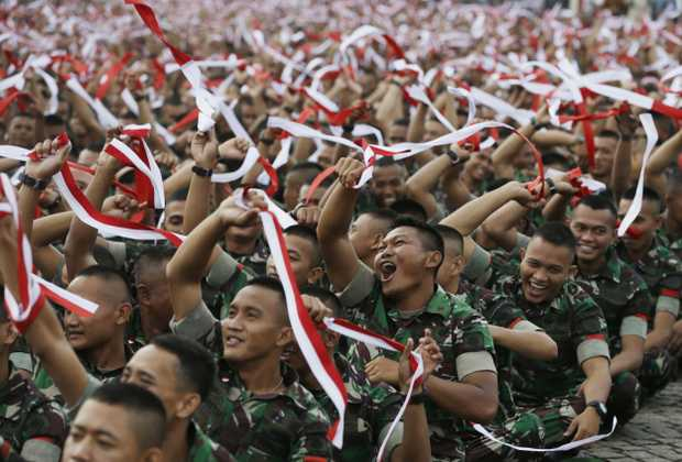 Indonesian soldiers hold up headbands in the color of the national flag during a military-sponsored interfaith rally. Source AAP.