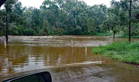 Fast flowing and dangerous: Nebo Creek is two metres over the road on Bowen Street, Nebo.