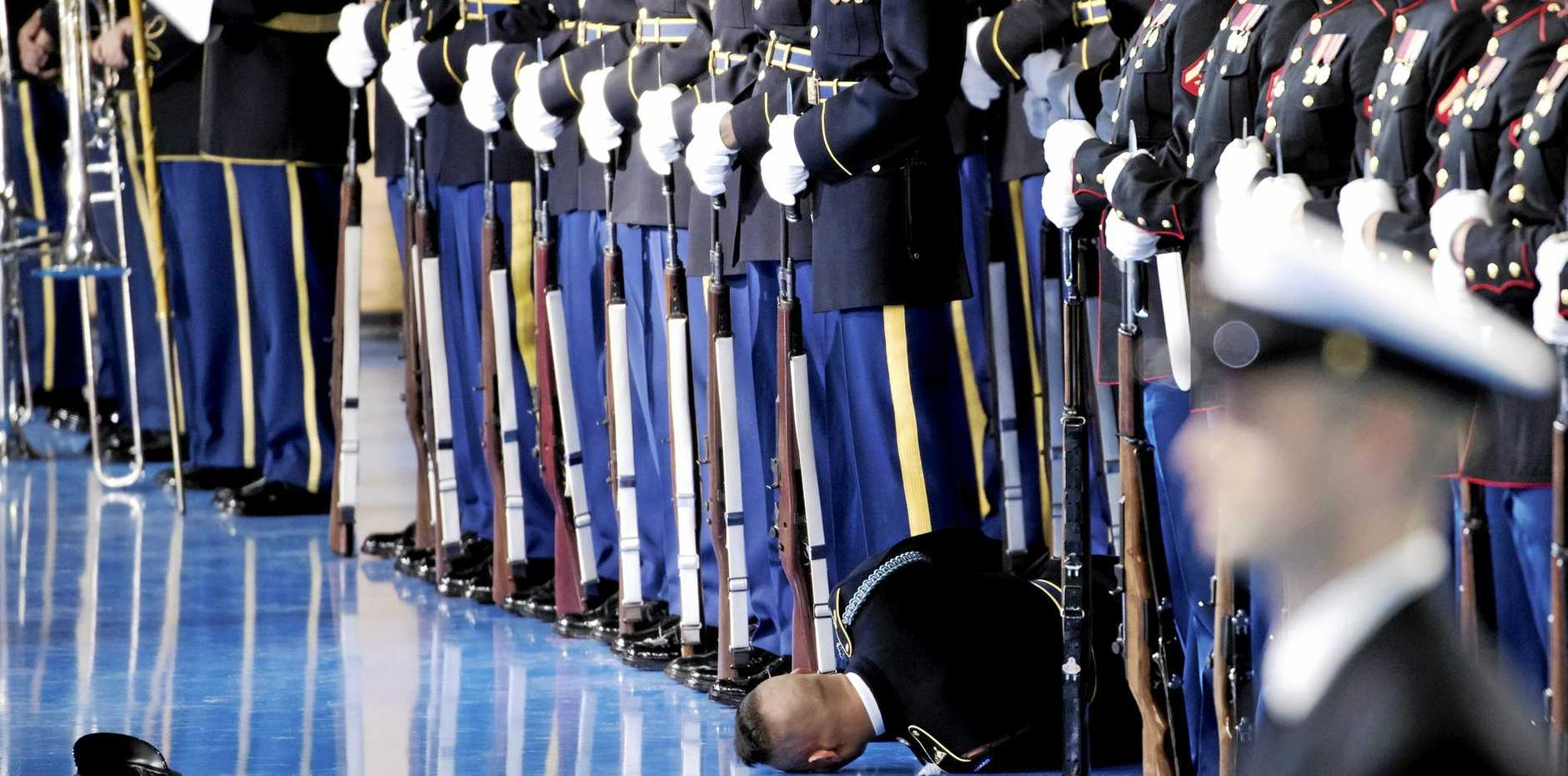 A member of the US Army honour guard lies on the floor after passing out during an Armed Forces Full Honor Review Farewell Tribute to US President Barack Obama at Conmy Hall, Joint Base Myer-Henderson Hall in Arlington, Virginia.