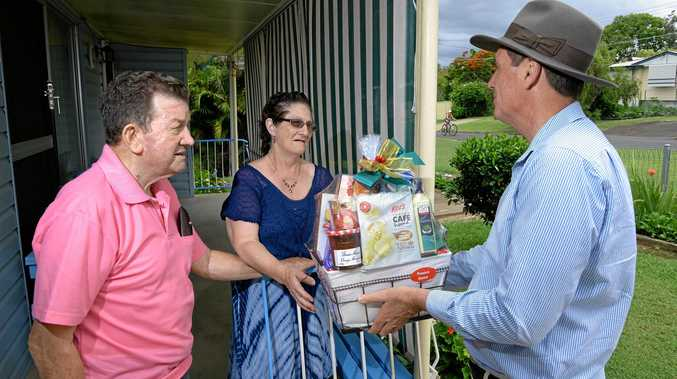 SORRY: Minister for Mines Anthony Lynham delivers a belated Christmas gift to Lynn and Ray McKay after their sink hole ordeal in Basin Pocket last year.