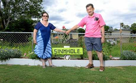 Lynn and Ray McKay stand next to the sign Ray made out of wood found in the sinkhole in their backyard.