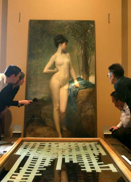 The famous painting titled Chloe is inspected for damage by experts Young and Jackson Hotel on Flinders Street in Melbourne, in 2004, following AFL grand final celebrations.