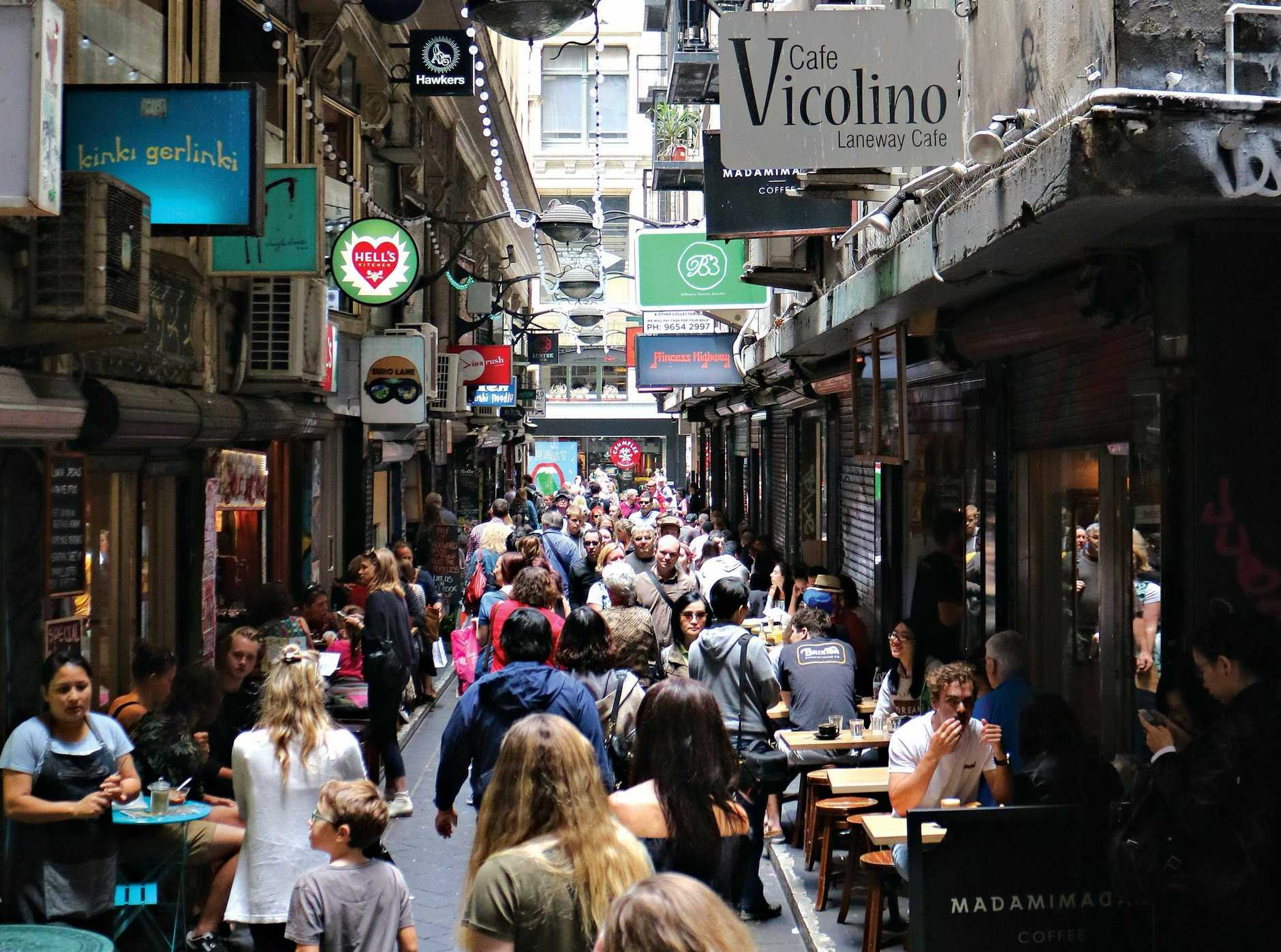 The opening of a narrow laneway in Melbourne's central business district reveals a number of cafes and bars lining the walkway.
