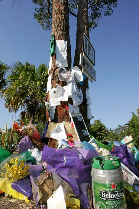 Tributes rest against a tree in Karawatha Drive in the days after three teenagers were killed in a crash.
