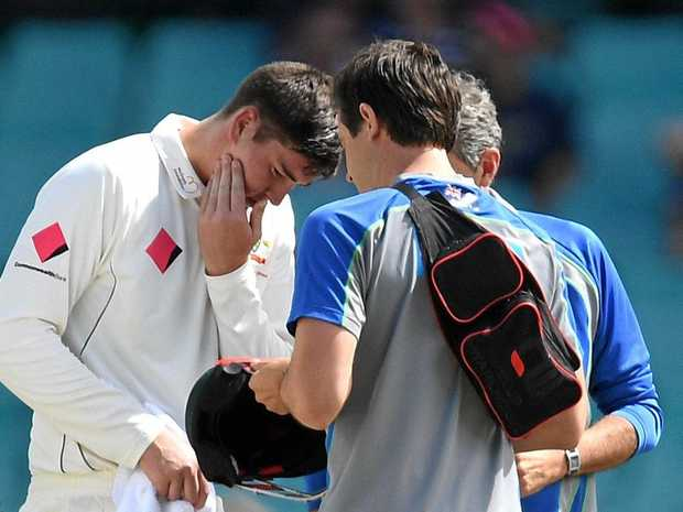 HEAD KNOCKS: Matt Renshaw of Australia receives attention after being hit on the helmet during his century on Tuesday.
