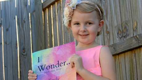 Four-year-old Audrey Pettit with her book I Wonder... Kindy.