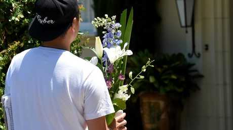 A courier delivers flowers to the Hird family home on Friday.