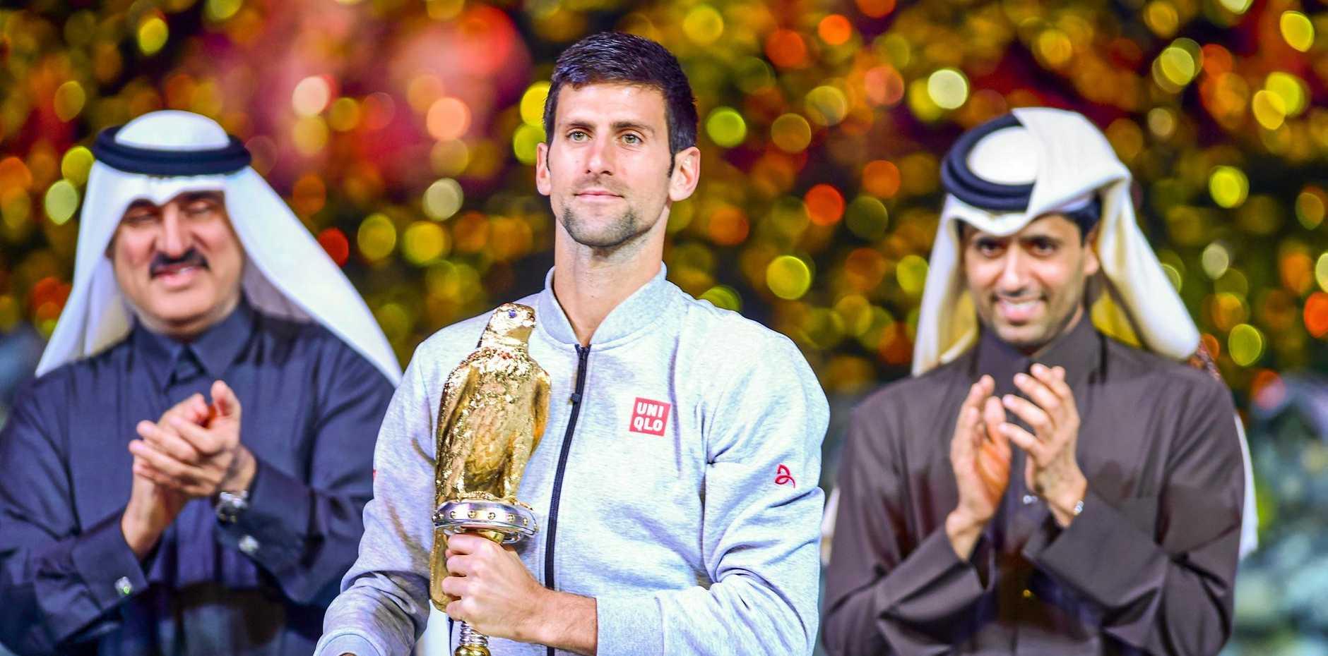 Novak Djokovic of Serbia celebrates with his trophy after winning the Qatar ExxonMobil Open.