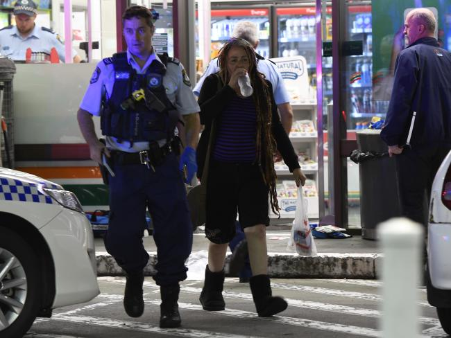 Sharon Hacker leaves the crime scene accompanied by an officer as police swarm over the 7-Eleven in the aftermath of the attack.