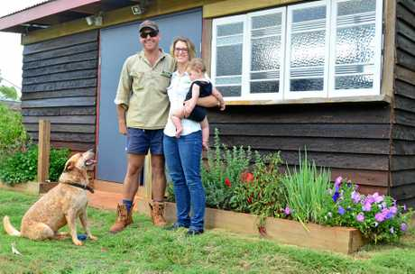 RECYCLING: Eco Lodge owners Rhys and Vanessa Kummerow, pictured with Digger and baby Sebastian, in front of the kitchen they have built with recycled local materials. Photo: Isis Town & Country / Eliza Goetze