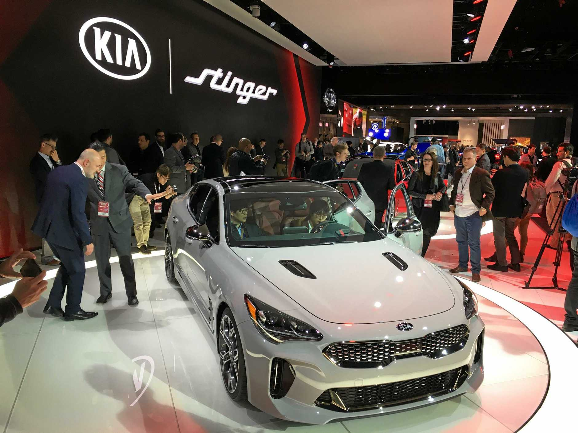 Crowds gather around the Kia Stinger GT at the Detroit motor show.