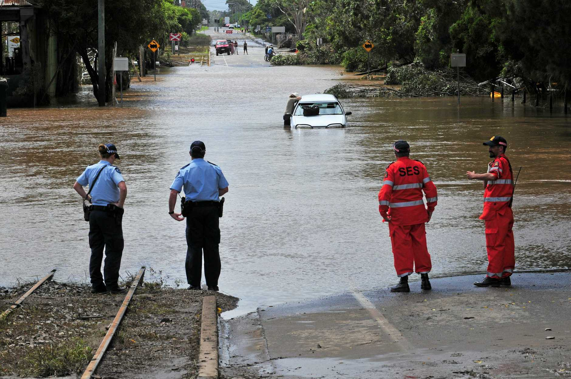 Police and SES stand watch over a motorist who's vehicle stalled in flood waters on Kent Street, Maryborough yesterday.      Photo: Nat Bromhead / Fraser Coast Chronicle