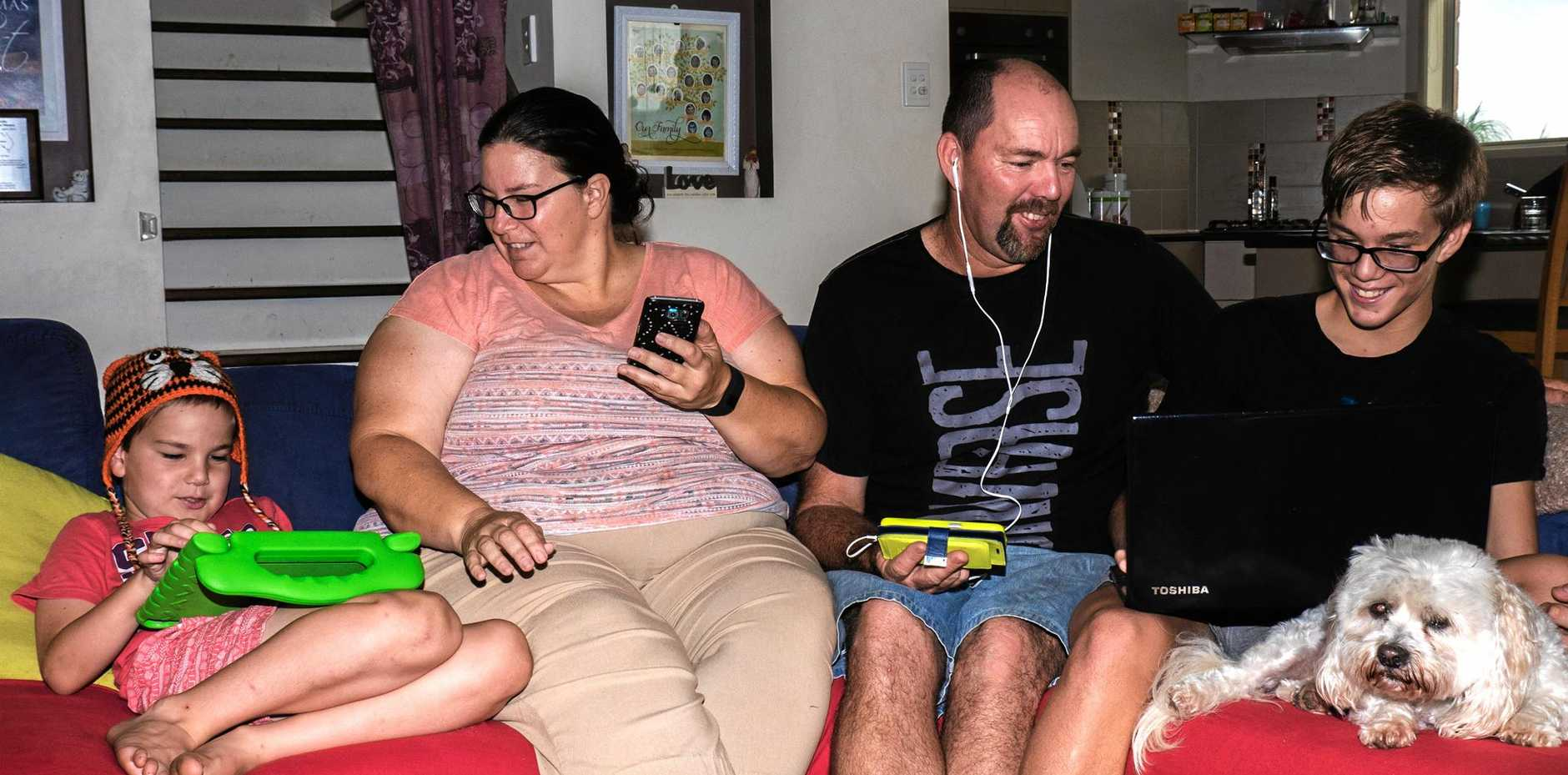 Gympie West's Micah, Kathy, Rob and Mitchell Pitt, with their dog Winston, enjoying their devices through the National Broadband Network.