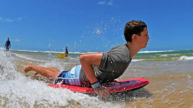 HEAT IS ON: Liam Hearn, 15, skimming the shallows at Maroochydore Beach may have the right idea with a fading swell predicted for the weekend.