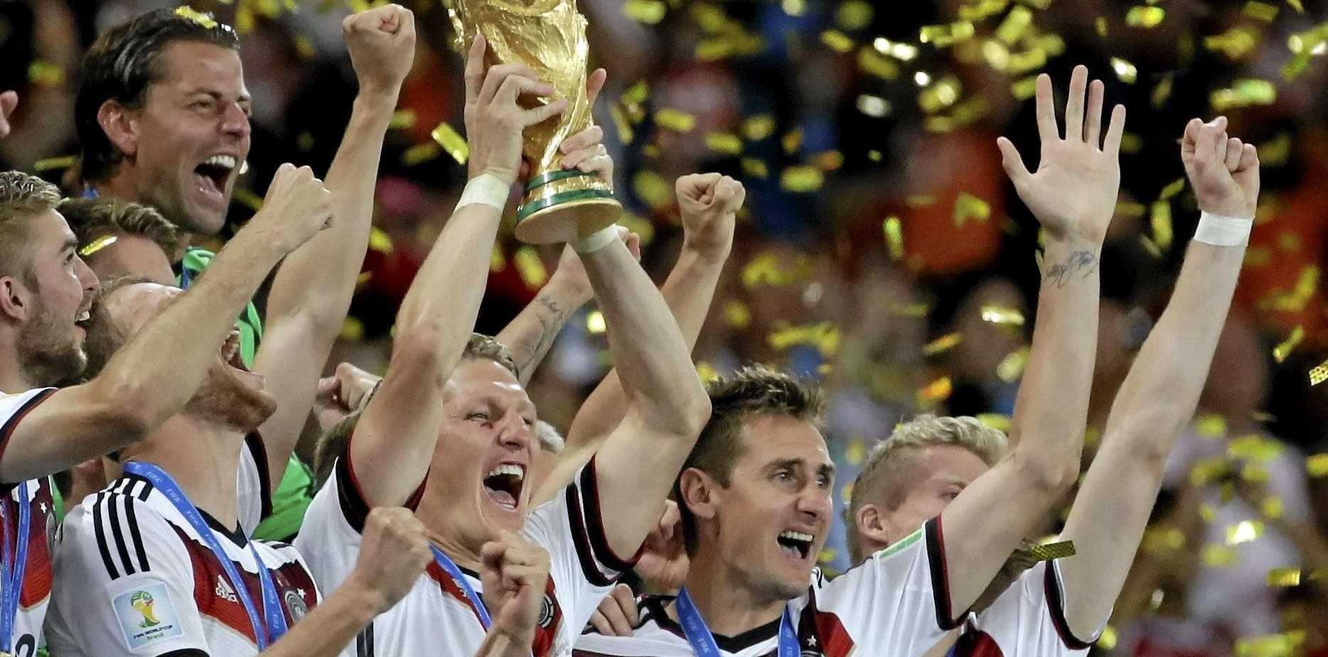 Germany's Bastian Schweinsteiger holds up the World Cup trophy as the team celebrates their 1-0 victor over Argentina after the World Cup final soccer match between Germany and Argentina at the Maracana Stadium in Rio de Janeiro, Brazil, Sunday, July 13, 2014. (AP Photo/Felipe Dana)