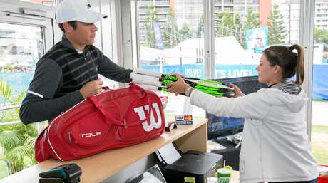 World Number 3, Milos Raonic, collects his racquets from the re-stringer.