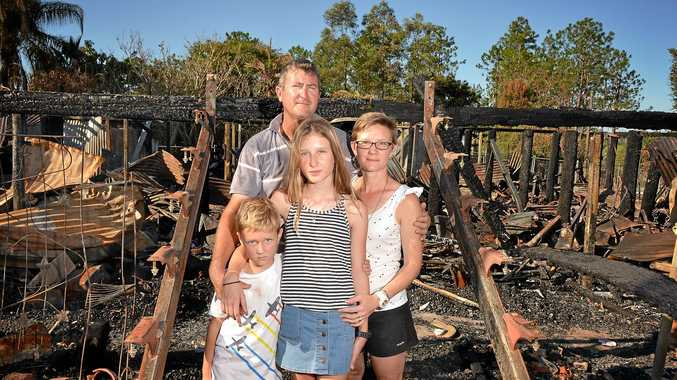 ASHES REMAIN: Col Gamble with children Lincoln and Rylee and wife Renae Gamble in the remains of their house after the fire.