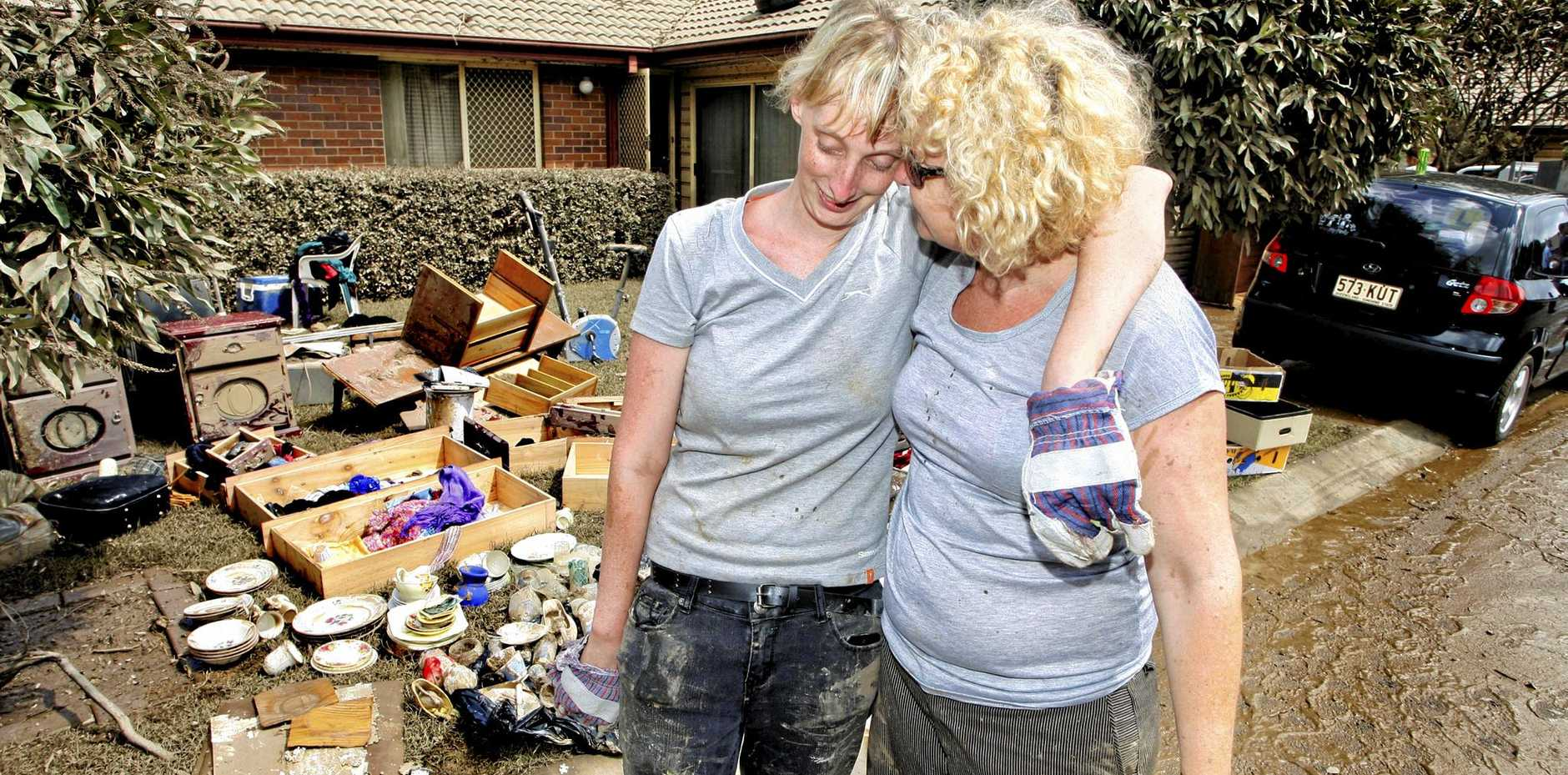 SUPPORT: The clean-up in Goodna in January, 2011 after major flooding. Goodna resident Benitta Harding is comforted by her friend Annie Walsh of Redbank Plains.