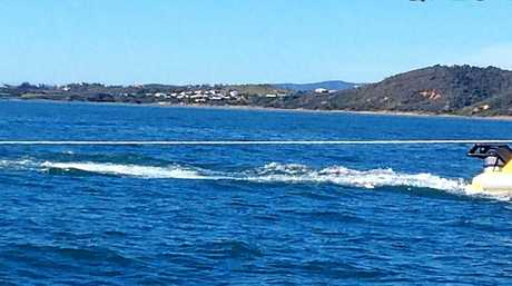 RMH Rescue towing the catamaran which capsized off the Capricorn Coast yesterday with a father and two children aboard.