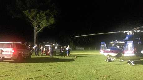 The RACQ CQ Rescue helicopter waits at Finch Hatton Showgrounds after winching crew members to assist the injured 19-year-old who fell down a cliff face at Finch Hatton Gorge.