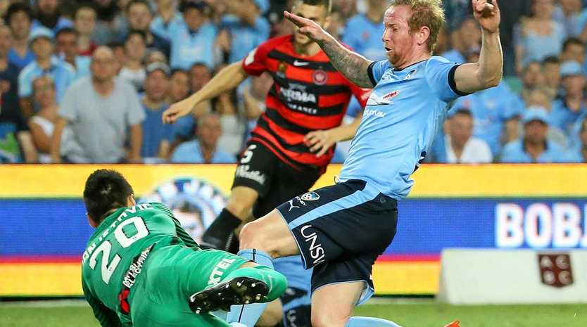 Wanderers goalkeeper Vedran Janjetovic dives on the ball ahead of Sydney's David Carney.