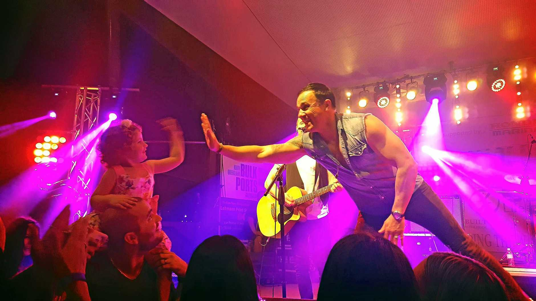 Three-year-old Lilli Carus gives Shannon Noll a high five during his performance at the Bowen Fishing Classic, September 17, 2016.