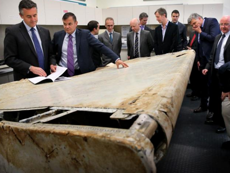 Minister for Infrastructure and Transport Darren Chester and ATSB Chief Commissioner Greg Hood and visiting aviation and air safety experts examine the right outboard main wing flap from MH370 in Canberra today.Source:News Corp
