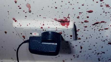 The mobile phone charger and bedroom wall was covered in blood.
