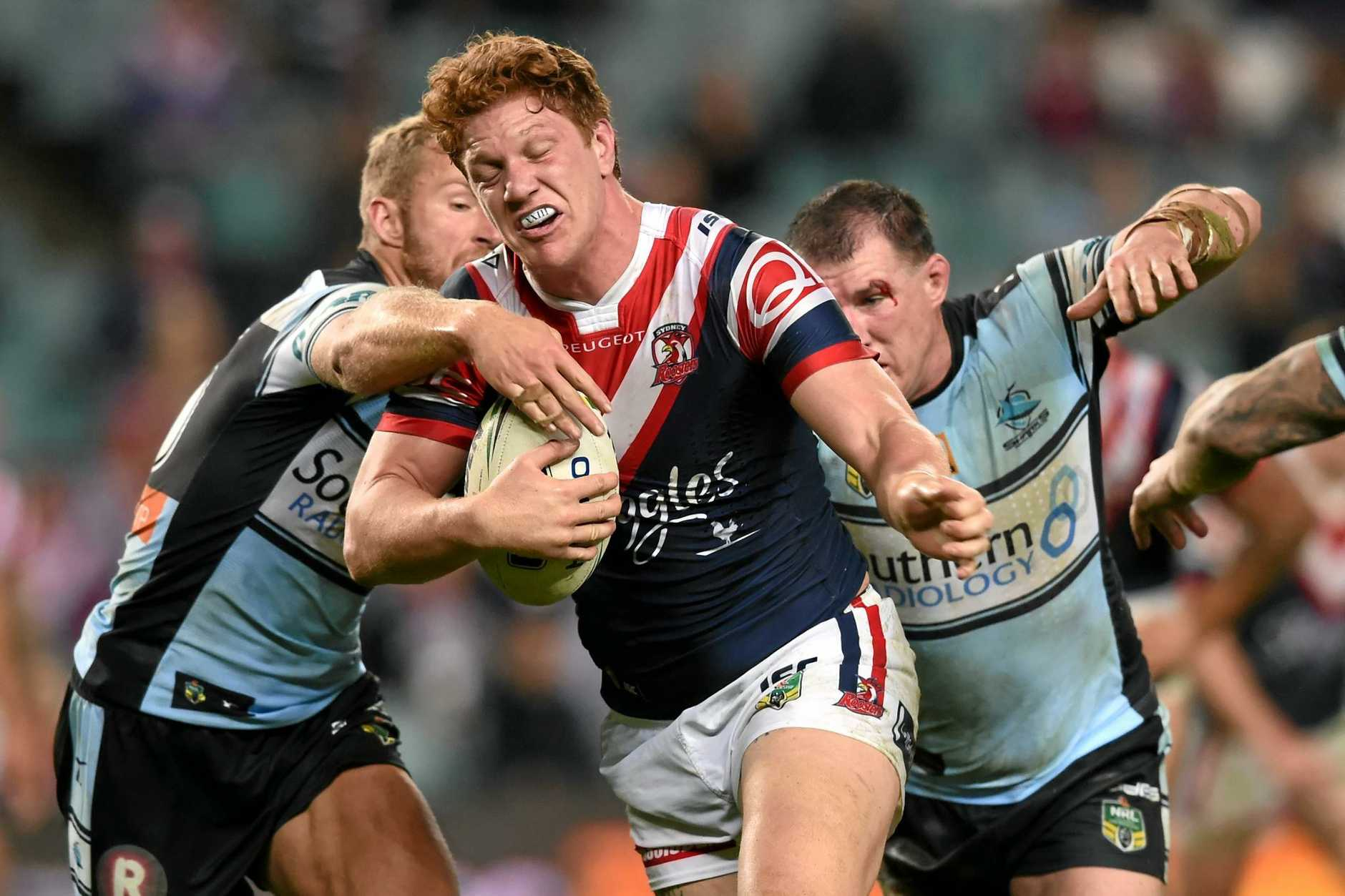 Dylan Napa of the Roosters is tackled by Paul Gallen (right) and Matt Prior of the Sharks last season.