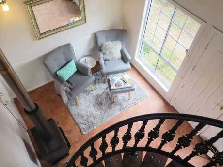 Modern downstairs living area with a gorgeous spiral staircase leading to the loft bedroom (queen bed) which has French doors opening to a private balcony.