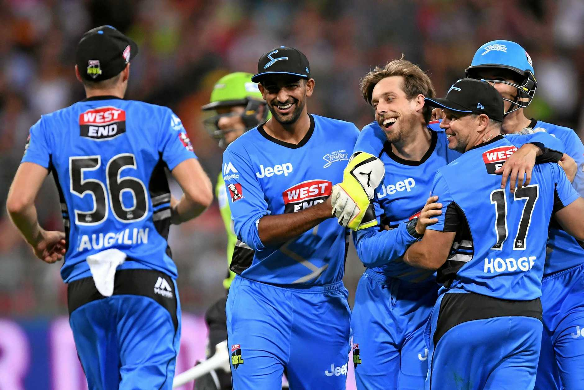 Jake Lehmann (centre) of the Strikers is congratulated after taking the wicket of Shane Watson of the Thunder