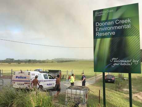 Police speak to residents at the Doonan Creek environmental reserve on Doonan Bridge Rd.