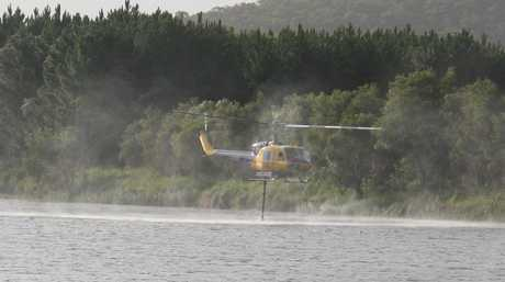 A helicopter fills up at a lake near the bushfire at Coolum.