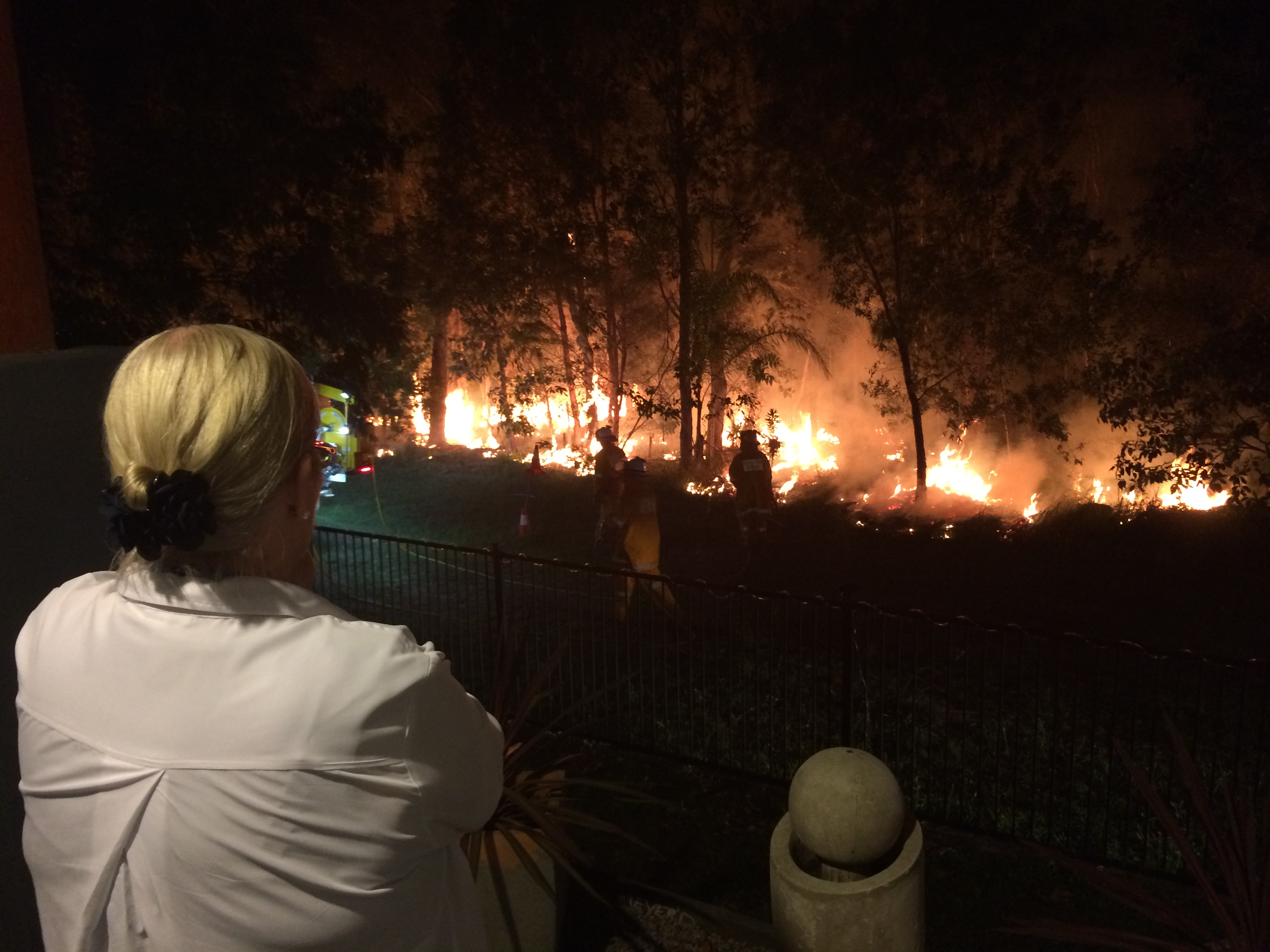 Roz Stuhmcke watches on as crews put in a back burn metres from her fence