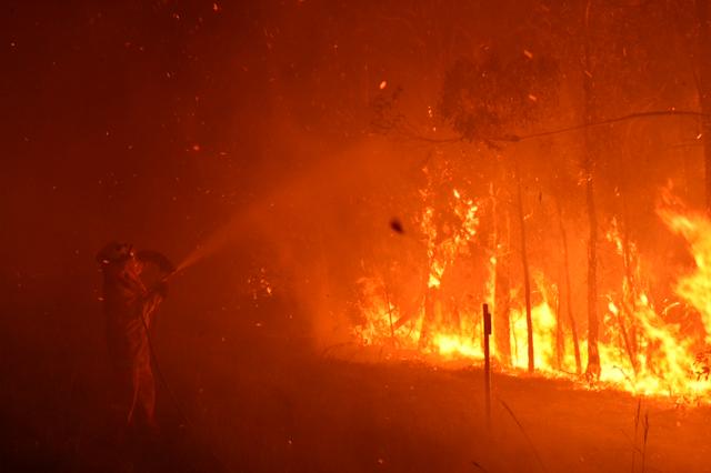 Firefighters spray a blaze at Peregian Springs