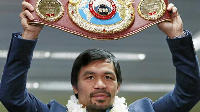Filipino boxer Manny Pacquiao raises his WBO welterweight championship belt.