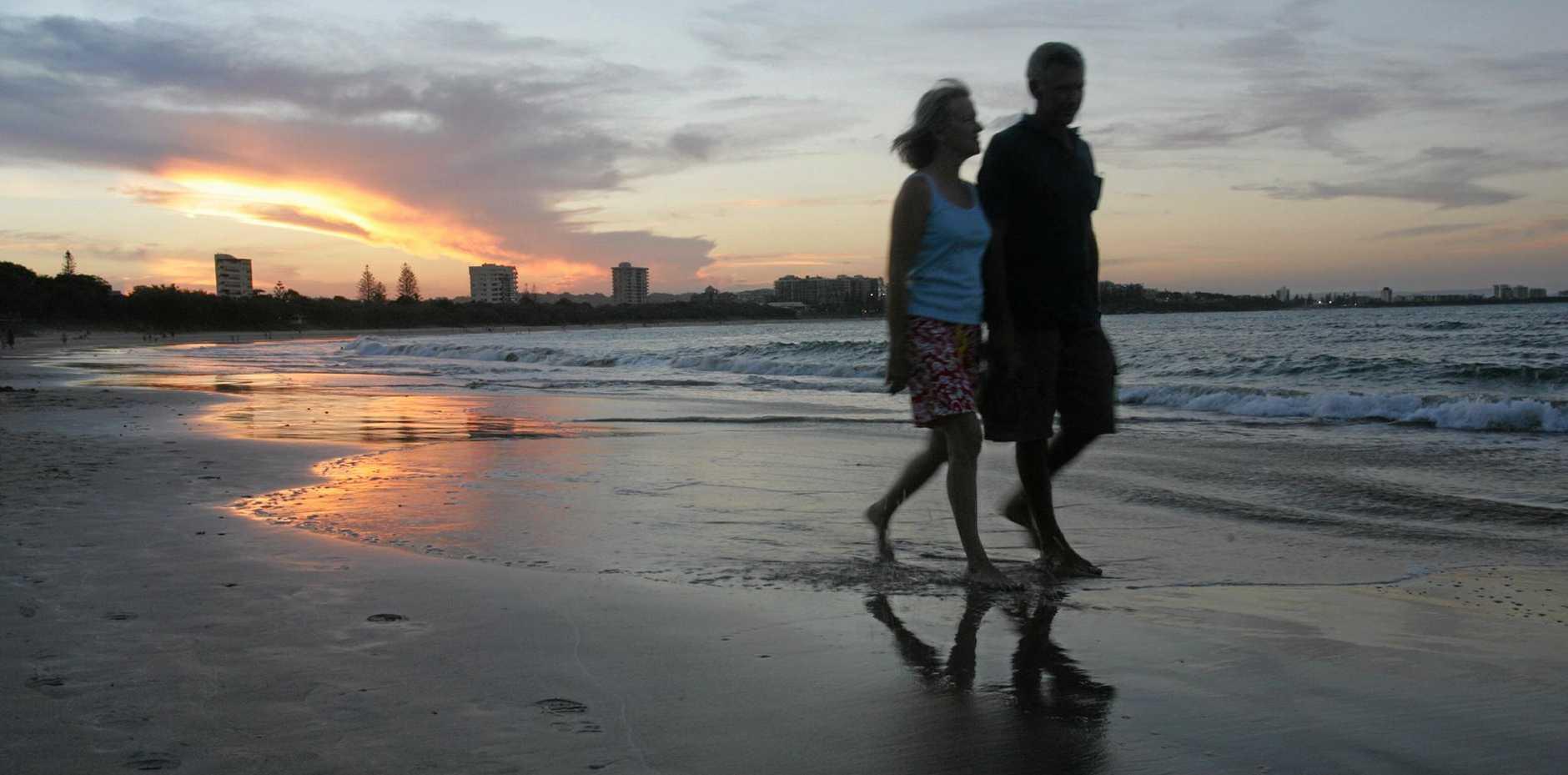 A couple walk hand in hand on Mooloolaba Beach.