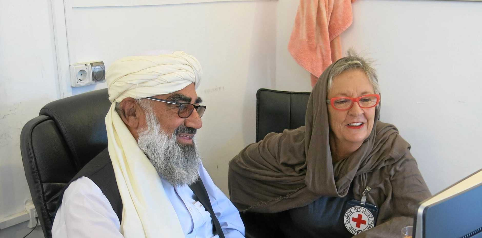 ICRC aid workers Kerry Page, reviewing the figures on Afghanistan's health program with the country's most experienced and longest serving Health Field Officer.