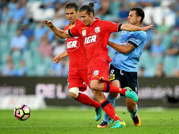 Michael Marrone of Adelaide United (centre) is tackled by Bobo of Sydney.