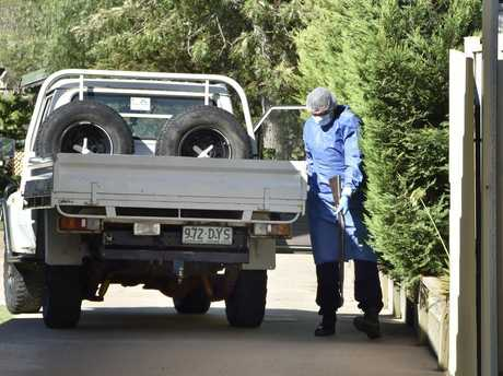SHOTS FIRED: A Police SOC officer removes a fire arm from a ute in the driveway of a Rudd St home. A crime scene has been declared at Rudd St, Drayton after shots were fired this morning.