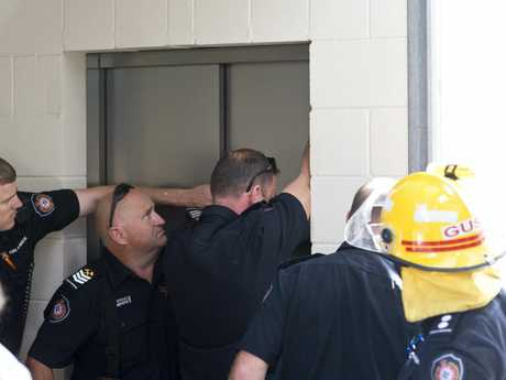 Firefighters work to free John Quade after he was trapped in a lift at the Blood Bank for an hour.