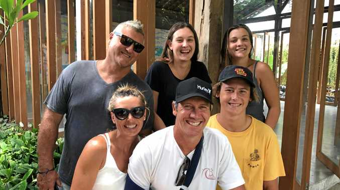 Shark attack survivor Dan Moore of Sunshine Beach with wife Kristina and son Max in the front row and mate Gary Emanuel, daughter Hayley Moore and Gary's daughter Olivia after his release from hospital in Bali.