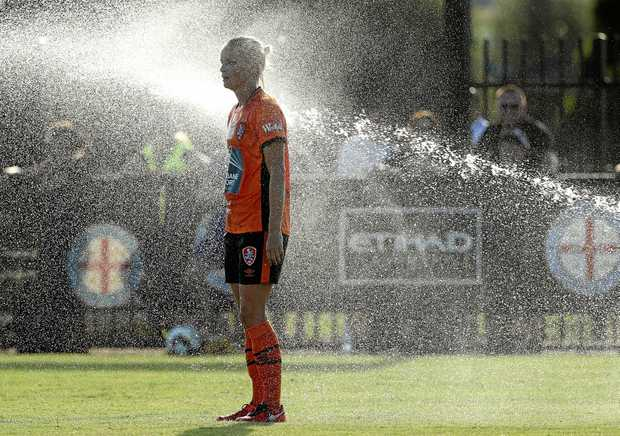 Nina Frausing-Pederson of Brisbane Roar stands under a sprinkler after it was switched on at C.B. Smith Reserve