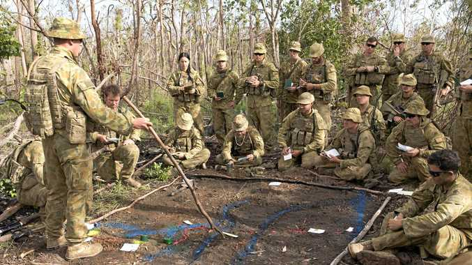 Australian Army officer Major Brent Hughes (left) from the 8th/9th Battalion, Royal Australian Regiment, delivers battle orders to unit personnel during Exercise Diamond Strike at Shoalwater Bay.